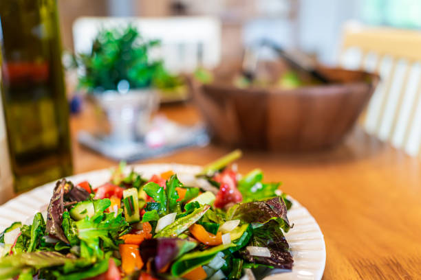 Closeup of plate with fresh green mixed lettuce salad in bowl background with bell peppers in rustic dining room wooden table stock photo