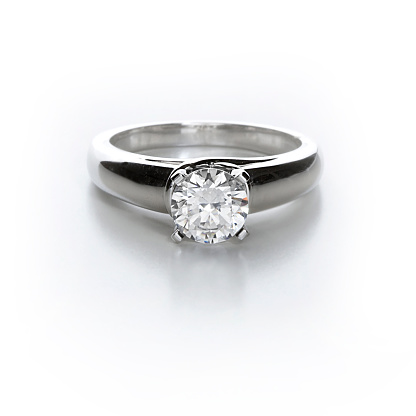 A diamond solitaire ring on white.