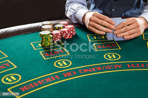 Close up of poker player with playing cards and chips at green casino table.
