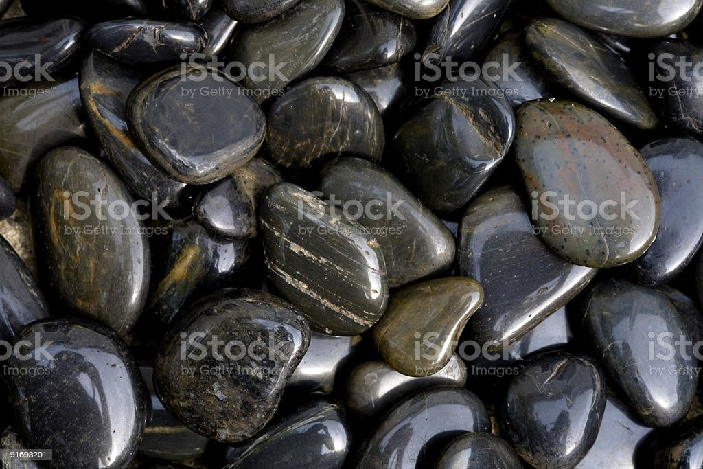 Closeup of Polished Shiny Dark River Rocks Background stock photo
