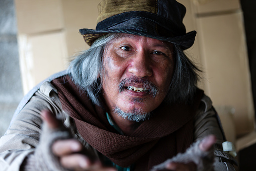 Closeup of poor old homeless asian man with brown hair, bearded, mustache, hat, gloves and blanket while raising his hands sitting on street in the city.