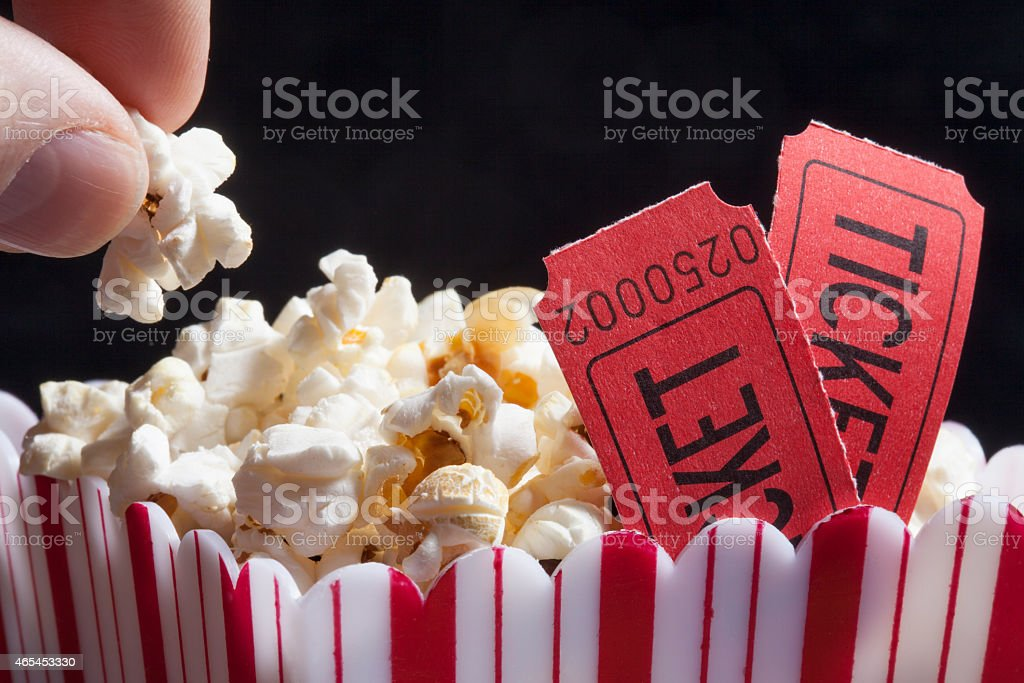 Close-up of popcorn bag with movie tickets stock photo