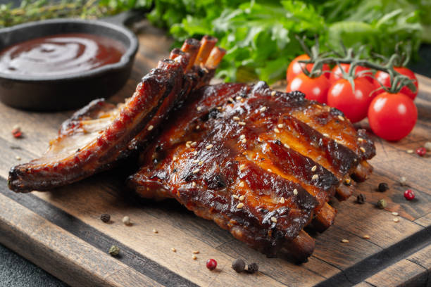 Closeup of pork ribs grilled with BBQ sauce and caramelized in honey. Tasty snack to beer on a wooden Board for filing on dark concrete background Closeup of pork ribs grilled with BBQ sauce and caramelized in honey. Tasty snack to beer on a wooden Board for filing on dark concrete background. pork stock pictures, royalty-free photos & images