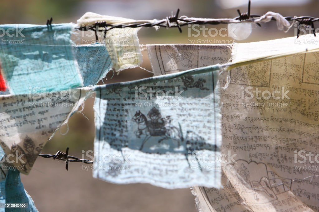 Closeup Of Prayer Flags On The Barbed Wire Of A Buddhist Temple In Paro  Bhutan Stock Photo - Download Image Now