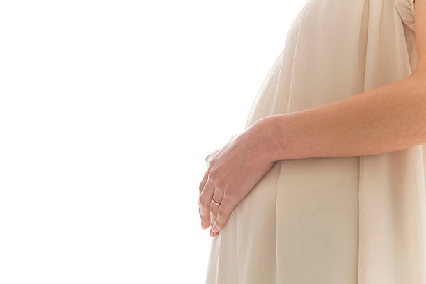 Close-up of pregnant Japanese woman with hands on stomach ストックフォト