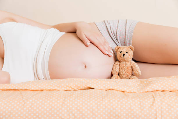 Closeup of pregnant woman with teddy bear lying on bed stock photo