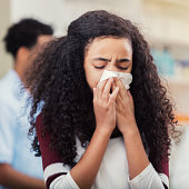 In this closeup, allergies are not fun as a preteen girl closes her eyes and draws a tissue up to her mouth with both hands and sneezes.