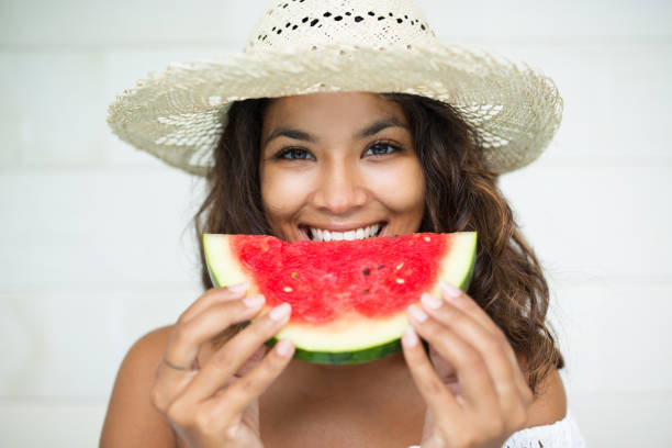 Closeup of Pretty Woman Eating Slice of Watermelon stock photo