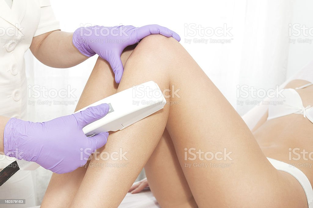 Close-up of professional administering laser hair removal stock photo