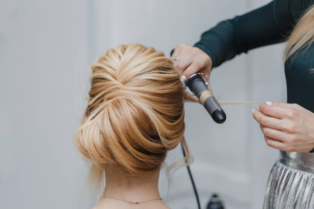 closeup of professional hairdresser hands doing beauty hairstyle a-la french twist closeup of professional hairdresser hands doing beauty hairstyle a-la french twist prom night stock pictures, royalty-free photos & images