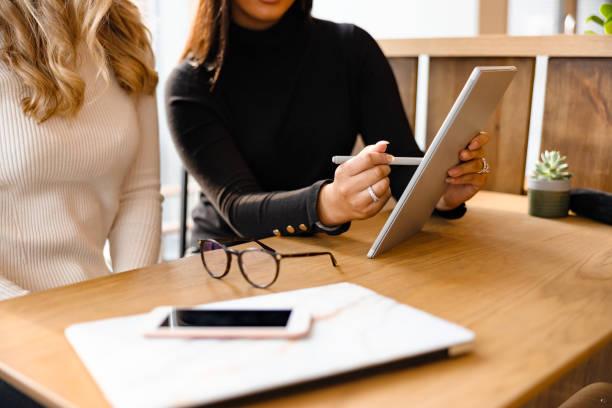 Nahaufnahme des professionellen Teams diskutiert über digitales Tablet im Cafe – Foto