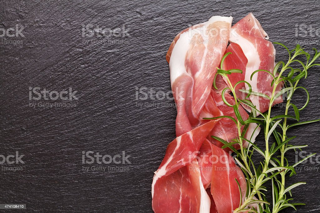 Close-up of prosciutto slices and rosemary sprigs stock photo