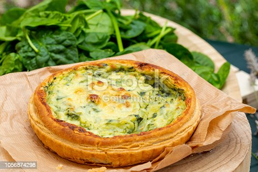 istock Close-up of quiche with fresh vegetables. Background in green tones. Rustic and country aspect. 1056874298