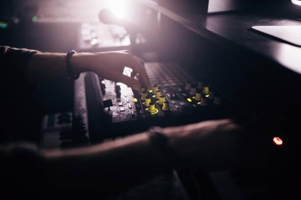 nahaufnahme von radio station dj arbeiten auf audio control panel - postproduktion stock-fotos und bilder