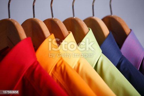 Rainbow colored shirts on hangers.