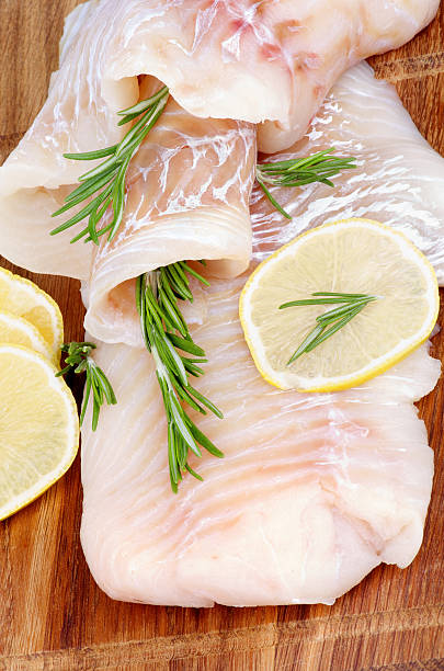 A close-up of raw cod fish with lemon stock photo