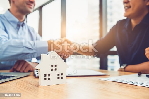 Closeup of real estate broker agent shaking hands with customer after signing contract agreement documents successfully with house property. Ownership realty purchase. Mortgage loan approval concept.