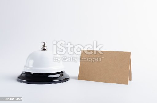 840883328 istock photo Closeup of reception call bell and table plate on the white background 1190581389