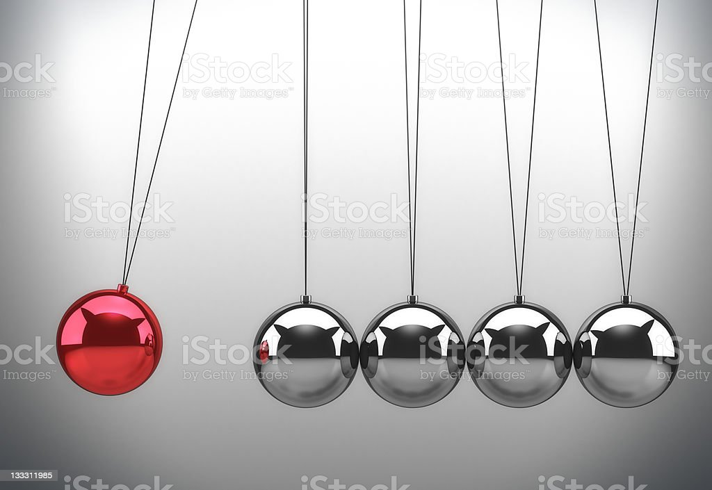 Close-up of red and silver Newton's cradle stock photo