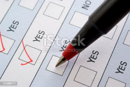 istock Close-up of red ball point pen marking a checkbox 124380711