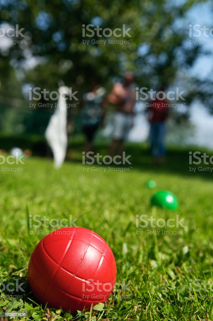 Closeup of red boccia ball lying in grass and people playing in background stock photo