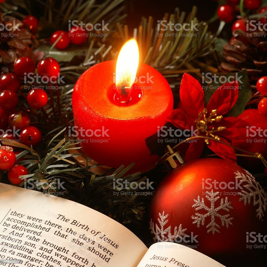 Close-up of red candle and bible with Christmas ornaments royalty-free stock photo