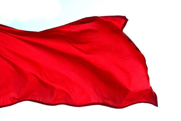 Close-up of red flag waving on white background Red Flag floating in the wind isolated on white background. red cloth stock pictures, royalty-free photos & images