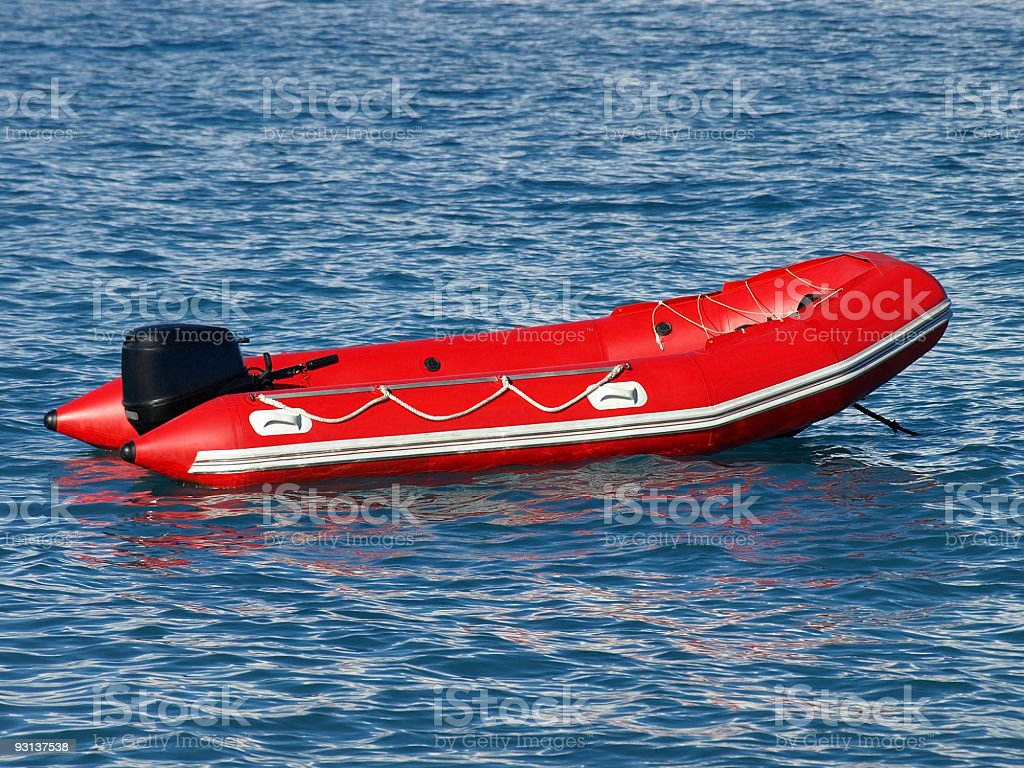 Close-up of red inflated lifeboat floating in water stock photo