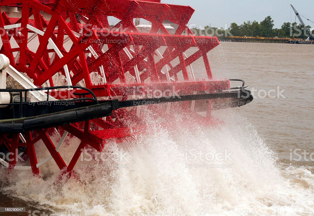 Close-up of red paddle boat wheel splashing in the water stock photo