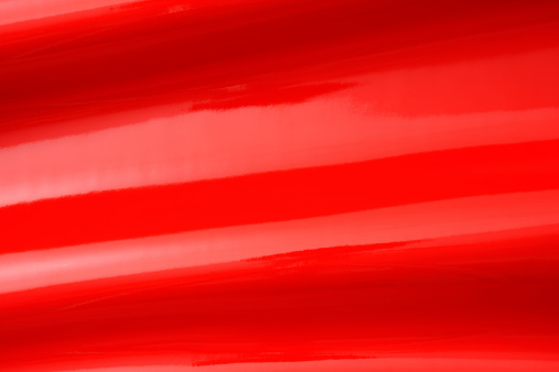 Close-up of red shiny vinyl wave texture background.
