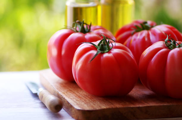 closeup of red tomatoes on wooden table stock photo