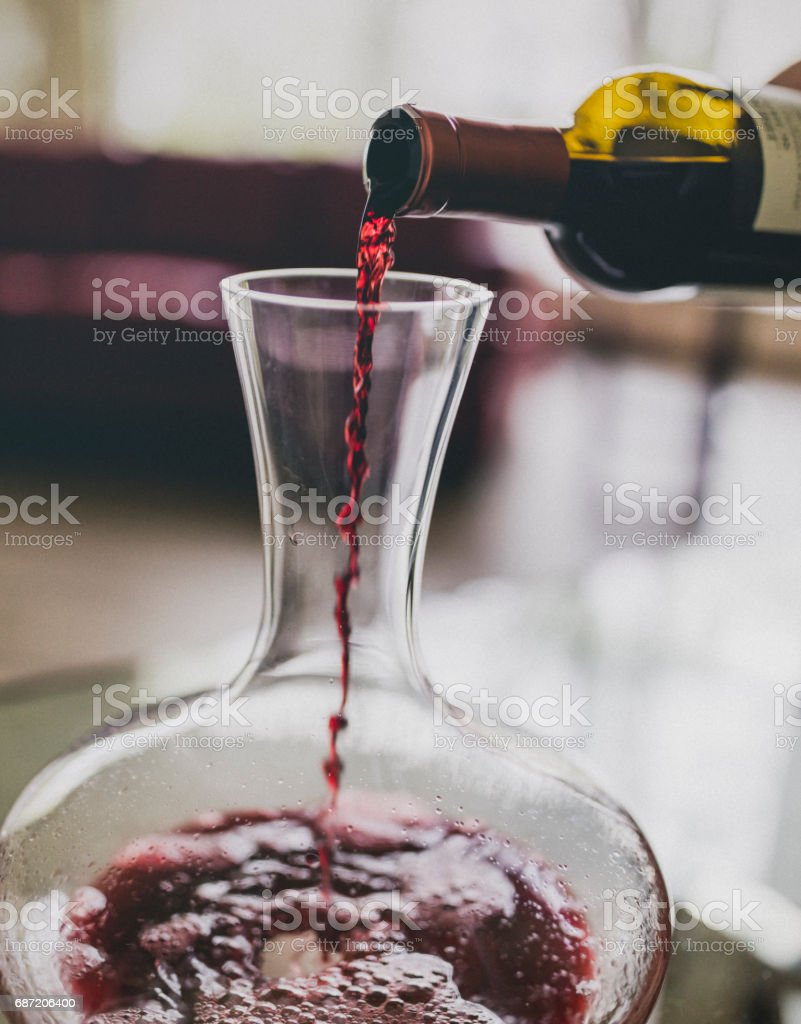 Close-up of red wine being poured in a wine decanter, part of the oxygenating process. stock photo