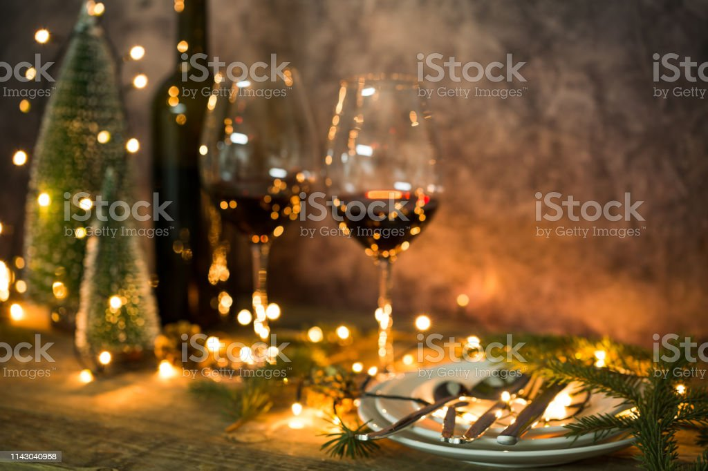 Closeup of red wine on table with Christmas lights. Christmas table and tree. - Foto stock royalty-free di Albero