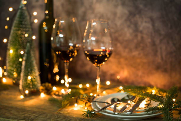 closeup of red wine on table with christmas lights. christmas table and tree. - cena natale foto e immagini stock