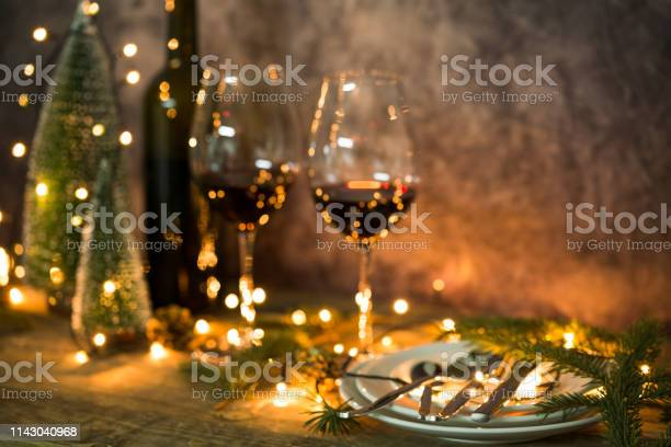 Closeup Of Red Wine On Table With Christmas Lights Christmas Table And Tree - Fotografie stock e altre immagini di Albero