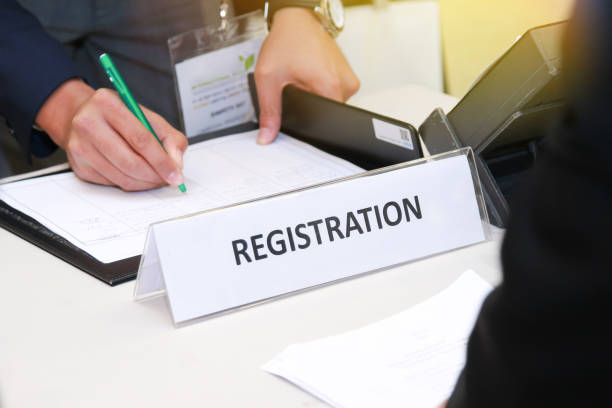 close-up of registration desk in front of conference center with Businessman Writing on the Table man hands write register paper register stock pictures, royalty-free photos & images