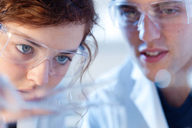close-up of research scienctists chemists working in laboratory horizontal - science research stock photos and pictures