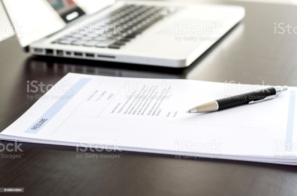 Close-up of resume, pen and computer laptop on black wooden desk. stock photo