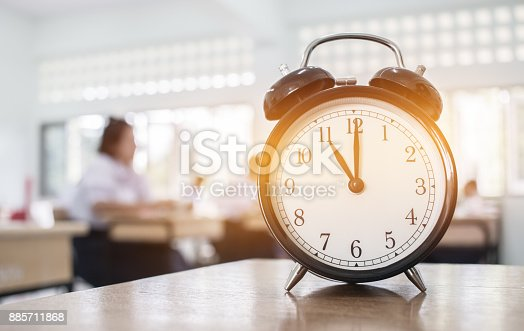 istock Closeup of Retro alarm clock with ten o'clock on table teacher in blur students exams classroom. Time is indefinite continued progress of existence. Education concept, selective focus. 885711868