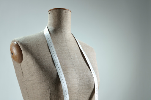 Close-up of retro female tailor's mannequin torso with measuring tape