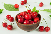 Close-up of ripe red sweet cherry with branches and leaves in a ceramic brown bowl on a white background. Selective focus.