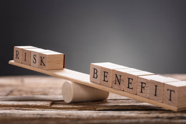 closeup of risk and benefit wooden blocks on seesaw - rischio foto e immagini stock