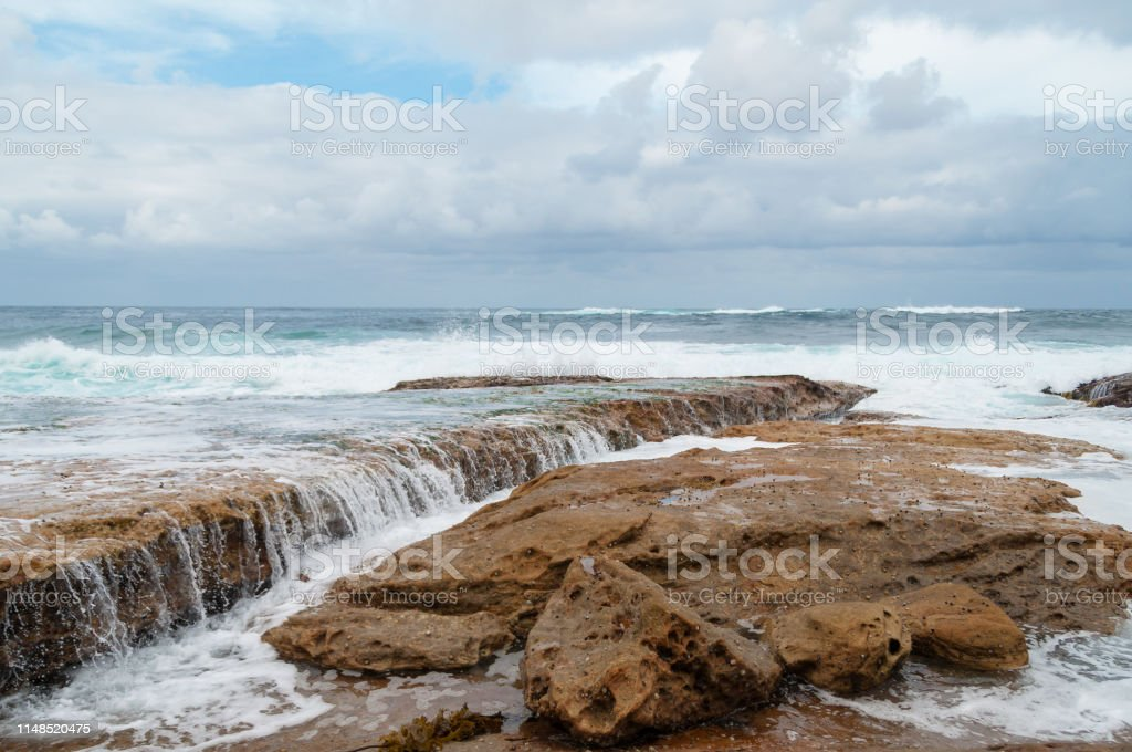 Close-up of rock formations near ocean shoreline with water flowing stock photo