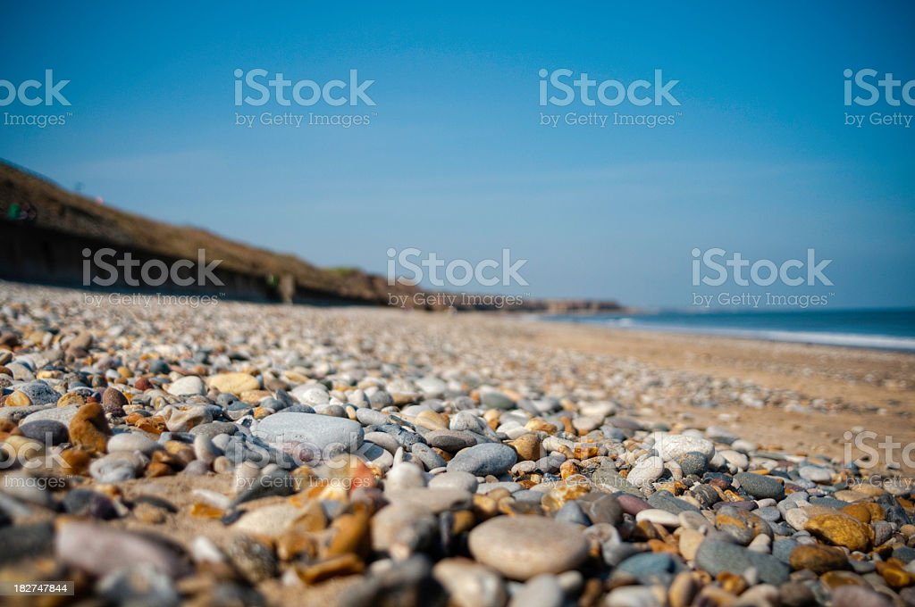 Close-up of rocks on a beach with blue sky behind stock photo