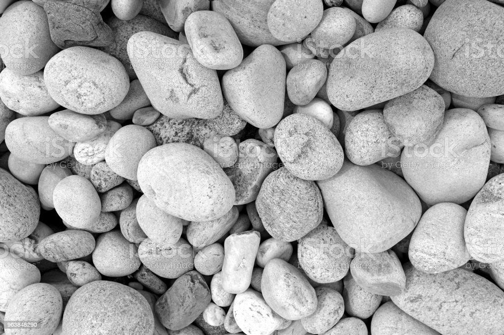 Closeup of rocks, pebbles and boulders on rocky beach which have been eroded smooth by the wave action of the water - Royalty-free Beach Stock Photo