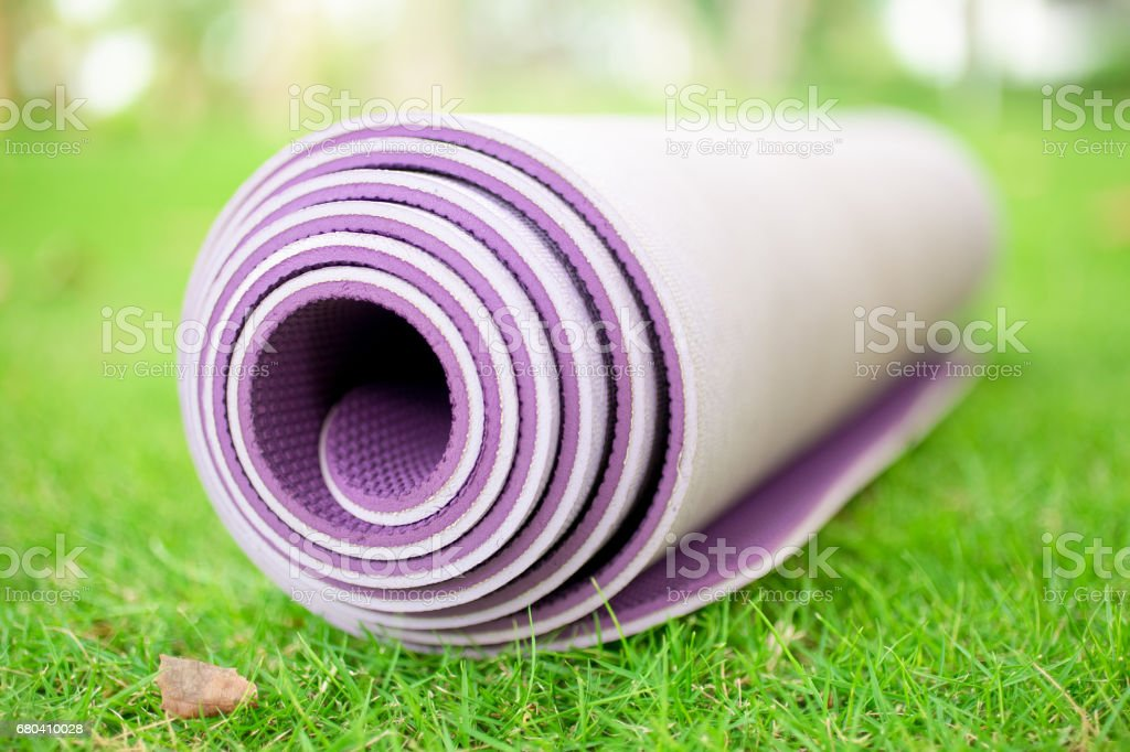 Close-up of rolled exercise mat on grass stock photo