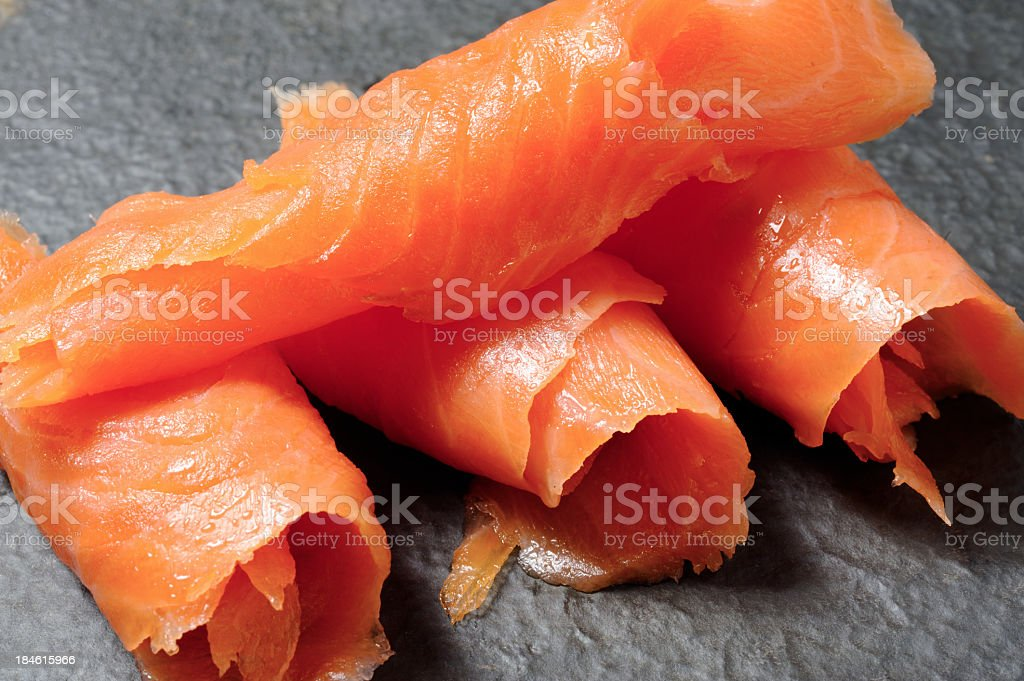 Close-up of rolls of smoked salmon on a gray background stock photo