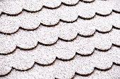 Pattern of a closeup of a roof with plane tiles covered with a thin layer of snow. Seen in Germany in December