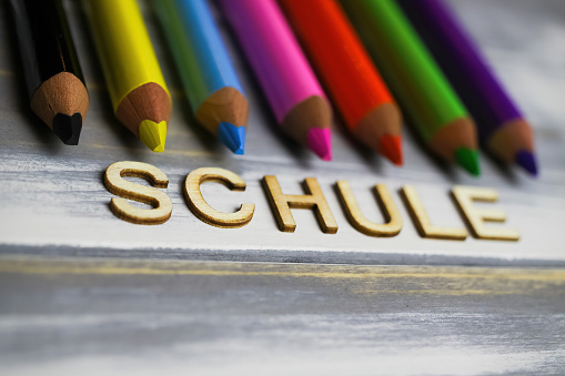 Closeup of row multi colored crayons on wood table with german word schule