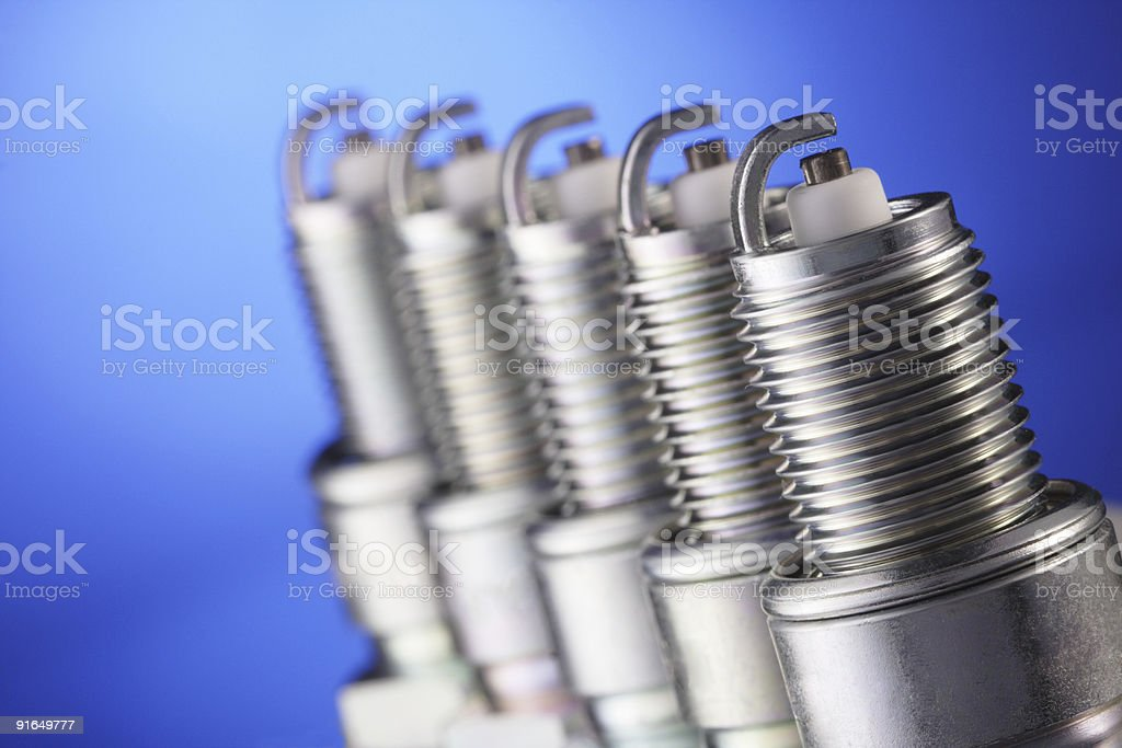 Close-up of row of spark plugs on a blue background royalty-free stock photo